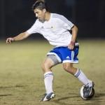 a man is kicking a soccer ball